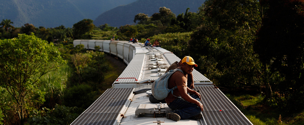 Honduran immigrants travel on top of a freight train on their way to the United States border in La Patrona
