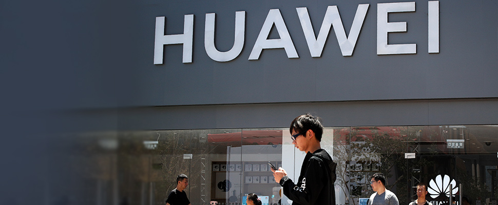People walk past a Huawei retail store in Beijing