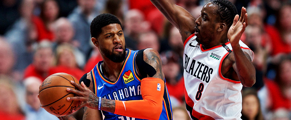Oklahoma City Thunder forward Paul George, left, looks to pass the ball around Portland Trail Blazers forward Al-Farouq Aminu