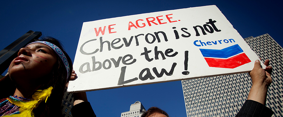 Ecuadorian protester holding a sign that says 'We agree, Chevron is not above the law'