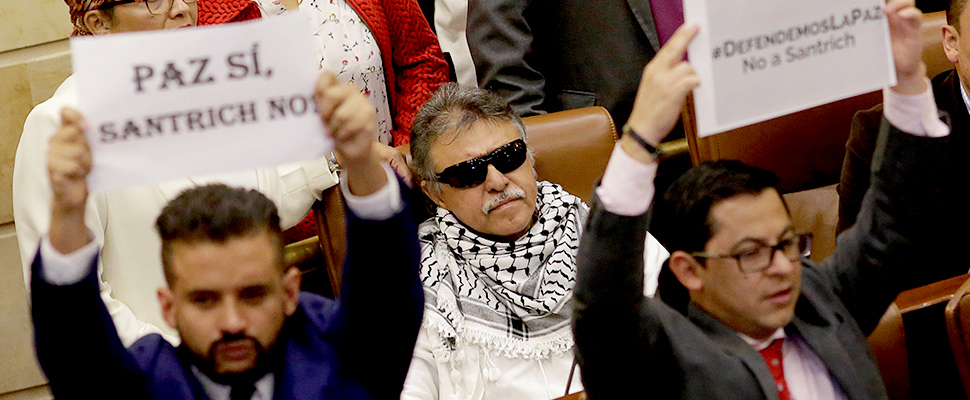 Congressmen hold signs against Santrich during a plenary session in the congress, in Bogota