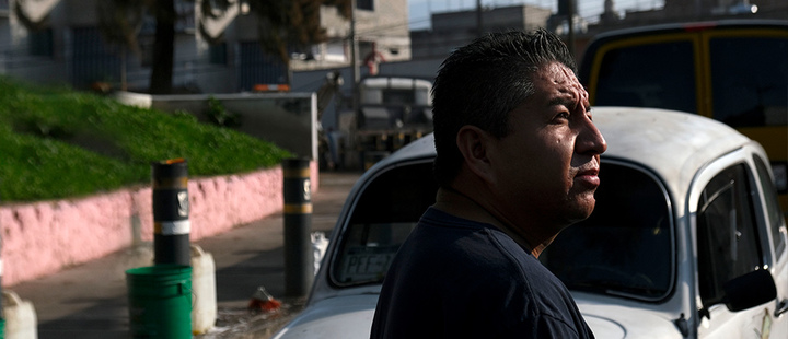Mechanic Bernardo Garcia stands in front of his Volkswagen Beetle