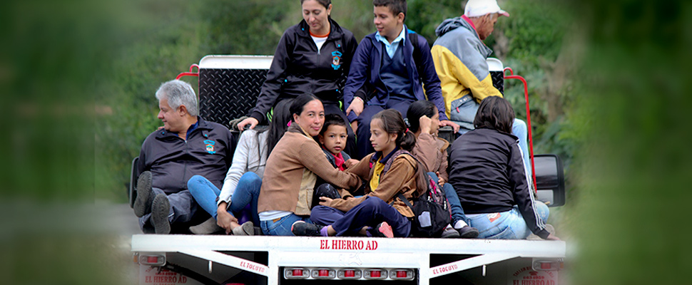Residents of a remote community catch a ride on the bed of a truck near