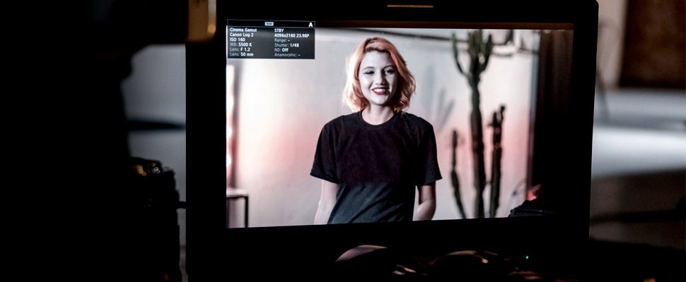 Woman in a recording set seen through a television screen
