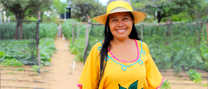 Lucero Granadillo in front of the garden growing fruits, vegetables and cereals in La Guajira