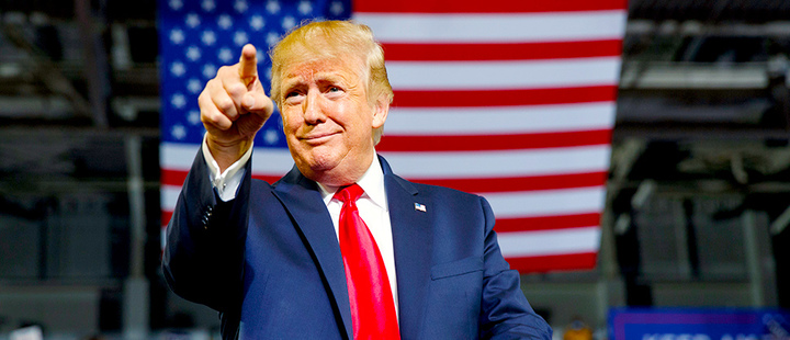 President Donald Trump gestures to the crowd as he arrives to speak at a campaign rally at Williams Arena in Greenville, N.C.