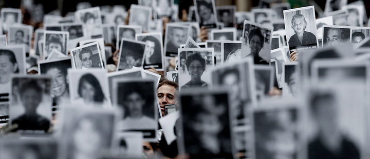 A man stands amid pictures of victims of the bombing of the AMIA Jewish center that killed 85 people, on the 25th anniversary of the attack in Buenos Aires
