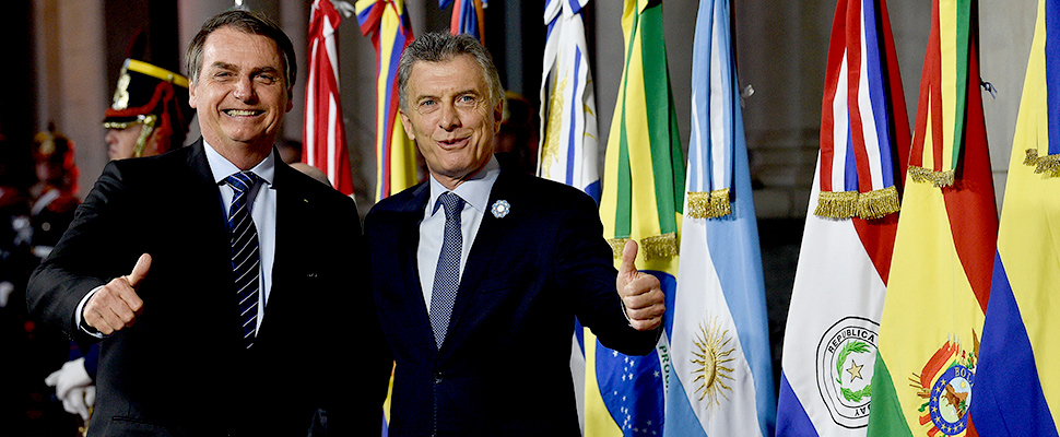 Argentina's President Mauricio Macri gives a thumbs up to photographers with Brazil's President Jair Bolsonaro at the Mercosur Summit in Santa Fe, Argentina