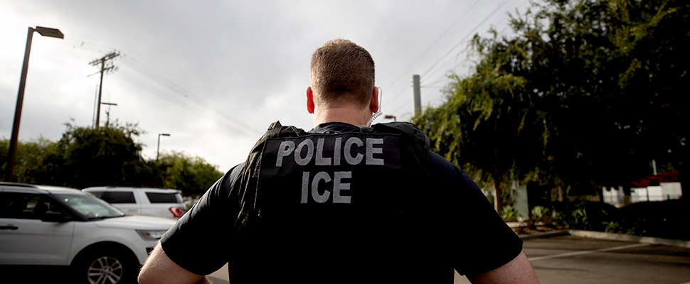 A U.S. Immigration and Customs Enforcement (ICE) officer looks on during an operation in Escondido, Calif.