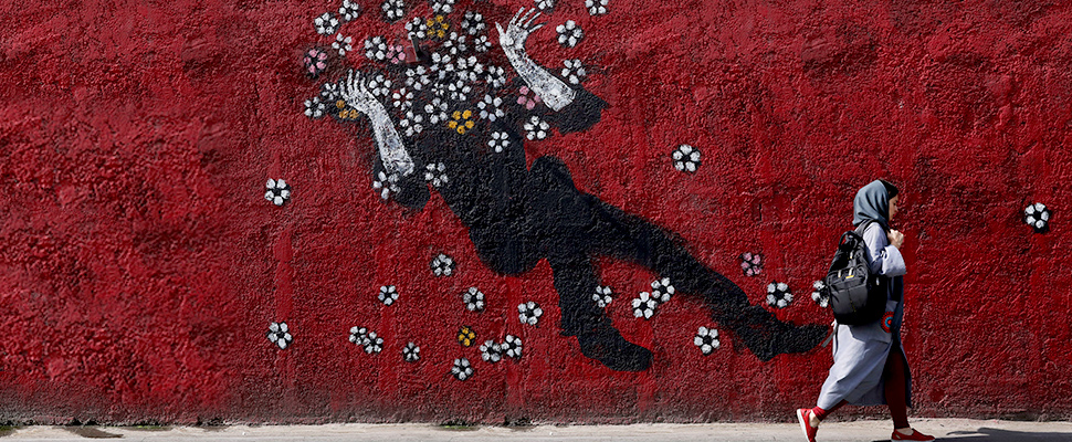 A woman walks past a mural in a sidewalk in downtown Tehran, Iran