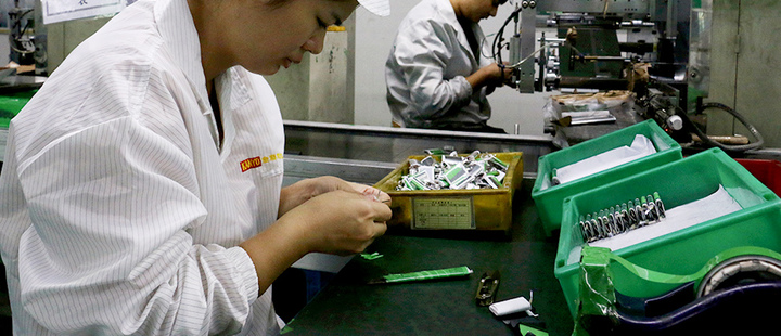 Employees work at a production line of lithium ion batteries inside a factory in Dongguan, Guangdong province, China