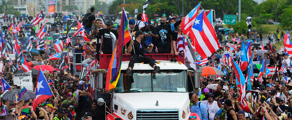 Puerto Rican singer Ricky Martin, front atop truck, participates with other local celebrities in a protest demanding the resignation of governor Ricardo Rossello in San Juan, Puerto Rico