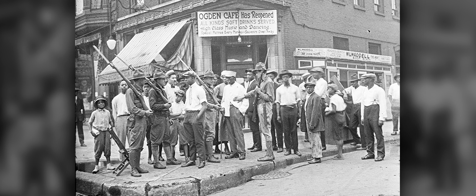 A crowd of men and armed National Guard stand in front of the Ogden Cafe during race riots in Chicago.