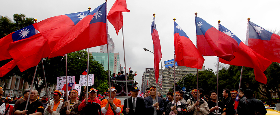 Activists holding Taiwan's national flags shout slogans during a rally near the Legislative Yuan, or Taiwan's parliament, in Taipei April 1, 2014.