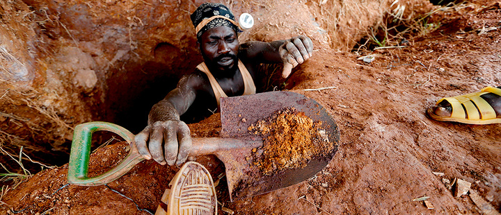 An informal gold miner carries a shovel as he climbs out from inside a gold mining pit at the site of Nsuaem-Top, Ghana