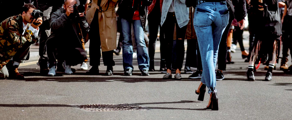 Woman wearing jeans walking on a street in front of photographers