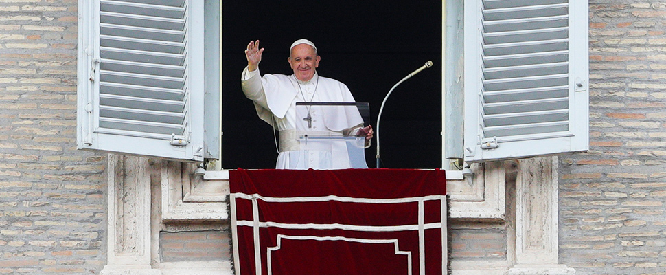 Pope Francis salutes from the window of his studio overlooking St. Peter's square at the Vatican, Sunday, July 28, 2019.