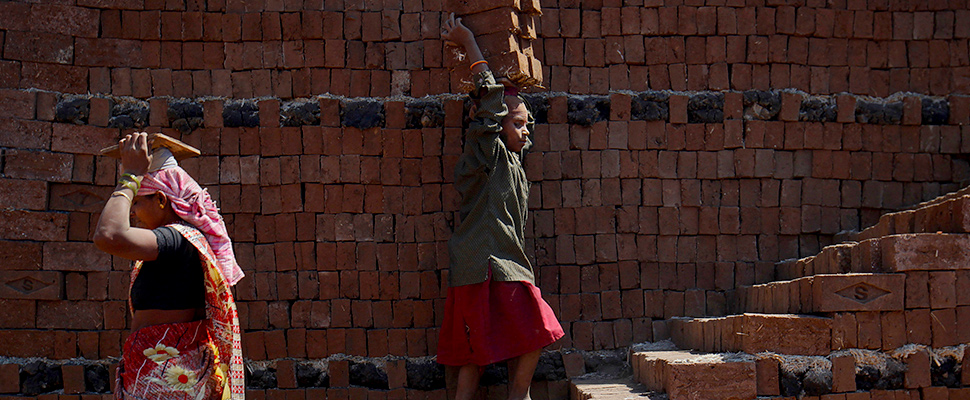 A girl carries bricks to be baked in a kiln at a brickyard on the outskirts of Karad in Satara district, about 396km (246 miles) south of Mumbai