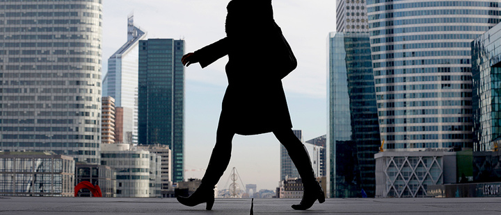 A Businesswoman is silhouetted as she makes her way under the Arche de la Defense, in the financial district west of Paris