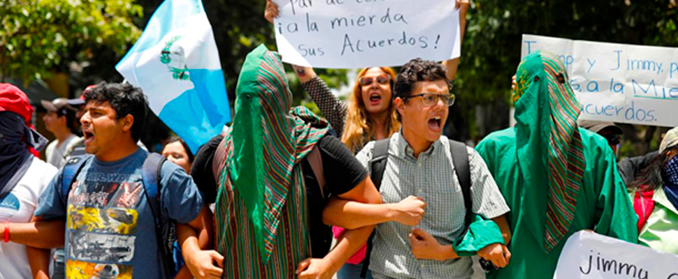 Protesters hold a protest in front of a hotel where lawmakers are working on an agreement in Guatemala City, Guatemala.