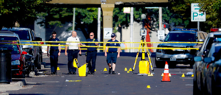 Authorities walk among evidence markers at the scene of a mass shooting, Sunday, Aug. 4, 2019, in Dayton, Ohio.