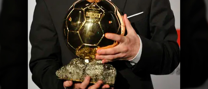 Lionel Messi holding a golden ball.