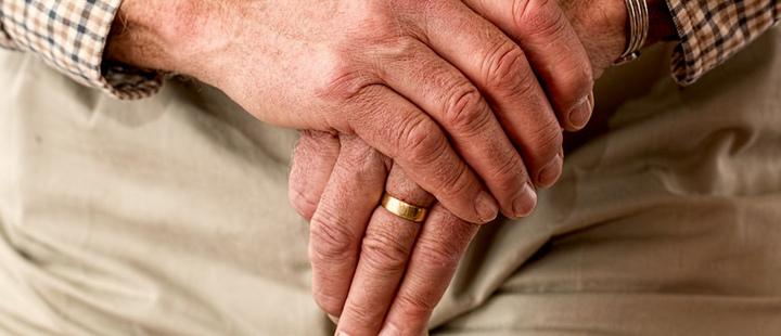 Hands of an elderly man on a cane