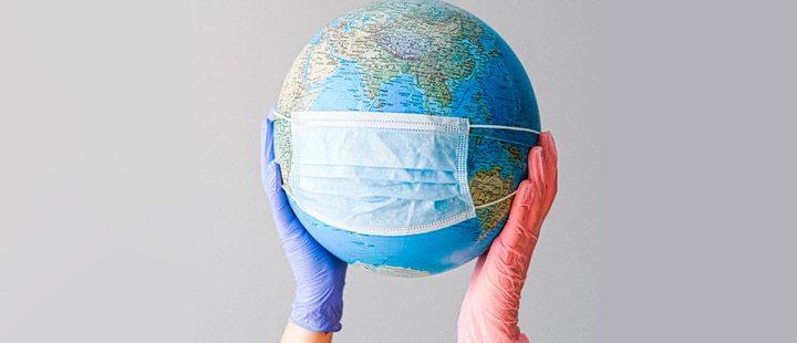 Manos sosteniendo un globo terráqueo con una máscara quirúrgica