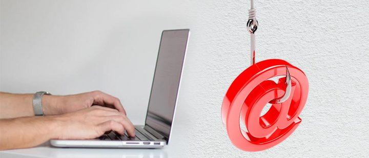 Persona usando un computador y símbolo de 'arroba' en una caña de pescar